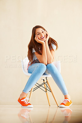 Buy stock photo Full length of cheerful young girl sitting on chair with head in hands and smiling sweetly at you - copyspace