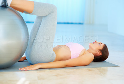 Buy stock photo Pretty young woman exercising with an exercise ball at gym - copyspace