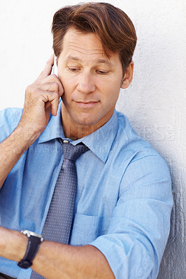 Buy stock photo Portrait of a busy young male executive using mobile phone and looking at watch