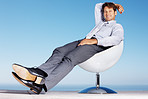 Relaxed businessman sitting on chair against sky