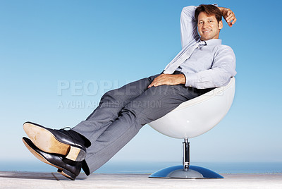 Buy stock photo Portrait of a happy young male business executive sitting relax on chair against sky