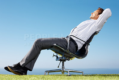 Buy stock photo Portrait of a handsome businessman sitting relaxed on a chair against sky