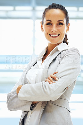 Buy stock photo Beautiful woman in business suit smiling at you with her arms folded confidently in a bright office copyspace
