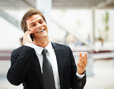 Buy stock photo Businessman smiling while having conversation on mobile phone
