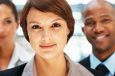 Buy stock photo Closeup of pretty executive with colleagues behind her