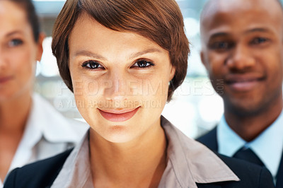 Buy stock photo Closeup of pretty executive smiling with peers in background