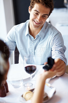 Buy stock photo Portrait of a young man giving a ring as a gift to a female in an outdoor cafe