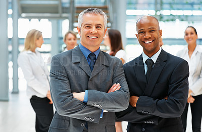 Buy stock photo Two businessmen smiling with arms crossed with team in background
