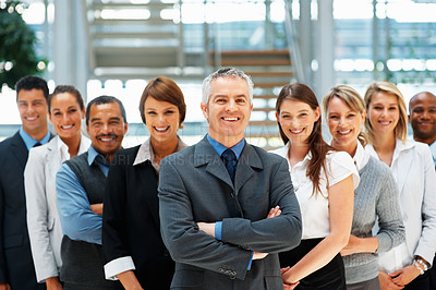 Buy stock photo Focus on senior man with colleagues behind him
