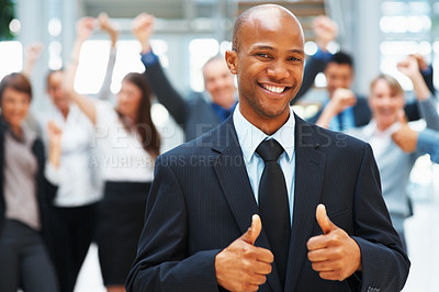 Buy stock photo Executive giving two-thumbs up with excited colleagues in background