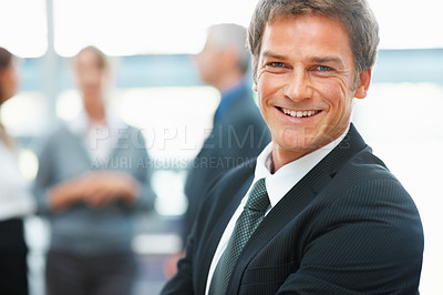 Buy stock photo Side view of happy businessman with colleagues in background