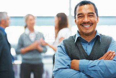 Buy stock photo Friendly executive with arms folded with colleagues in background