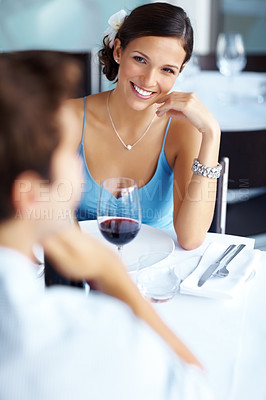 Buy stock photo Beautiful young woman looking at her boyfriend while sitting at restaurant with a glass of wine