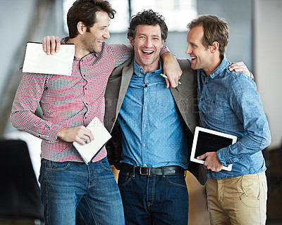 Buy stock photo Shot of a group of happy male colleagues standing arm in arm in an office