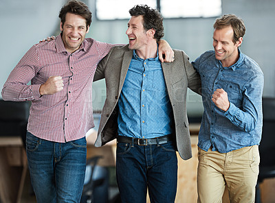 Buy stock photo Shot of a group of happy male colleagues celebrating arm in arm in an office