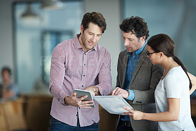Buy stock photo Shot of a group of coworkers standing in an office talking over a digital tablet