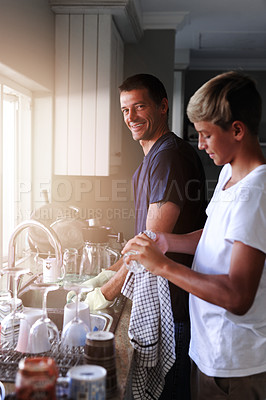 Buy stock photo Cropped shot of a father and son cleaning dishes together at home
