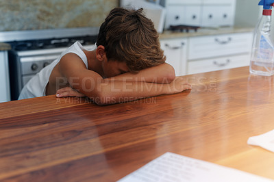 Buy stock photo Cropped shot of a young boy lying with his head on a table