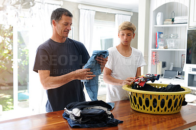 Buy stock photo Cropped shot of a father and son sorting through laundry together at home