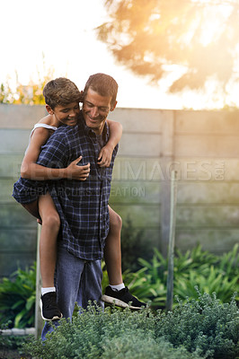 Buy stock photo Cropped shot of a father giving his son a piggyback ride outside
