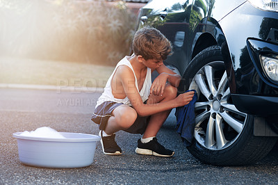 Buy stock photo Shot of a young boy washing the wheel of a car