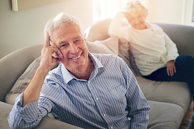 Buy stock photo Portrait of a senior man relaxing at home with his wife in the background
