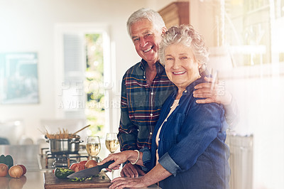 Buy stock photo Portrait of a senior couple cooking together in their kitchen at home