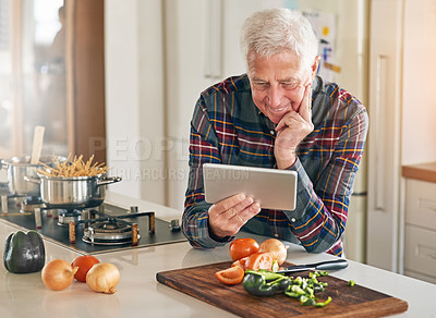 Buy stock photo Cropped shot of a senior man using a digital tablet while cooking in his kitchen