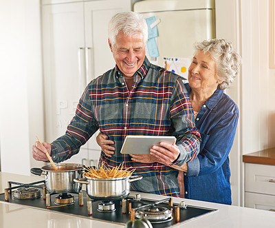 Buy stock photo Cropped shot of a senior couple using a digital tablet while cooking together in their kitchen at home