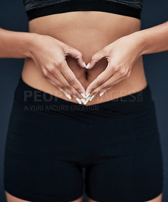 Buy stock photo Shot of an unidentifiable woman in sportswear make a heart shape with her hands over her stomach against a dark background