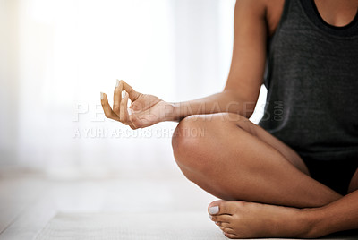 Buy stock photo Cropped shot of an unidentifiable young woman doing yoga by herself at home