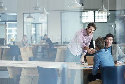 Buy stock photo Shot of two coworkers shaking hands at a table in an office