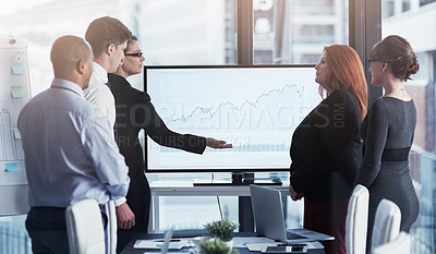 Buy stock photo Shot of a group of businesspeople talking together around a monitor with graphs while having a meeting in a boardroom
