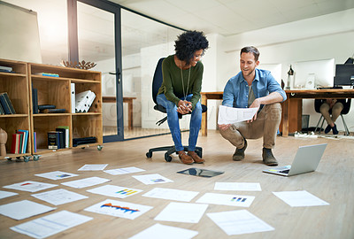 Buy stock photo Shot of entrepreneurs going through paperwork together in a modern office