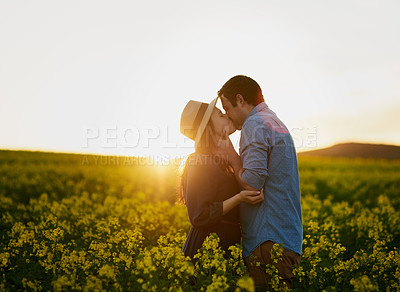 Buy stock photo Shot of an affectionate young couple sharing a kiss at sunset