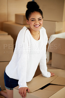 Buy stock photo Portrait of a happy young woman kneeling among cardboard boxes while moving house