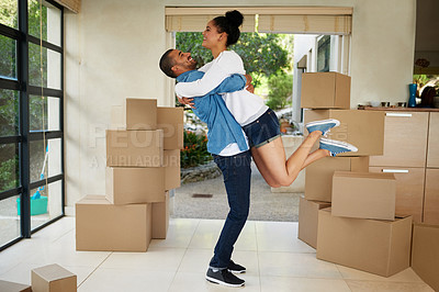 Buy stock photo Shot of a happy young couple celebrating their move into a new home