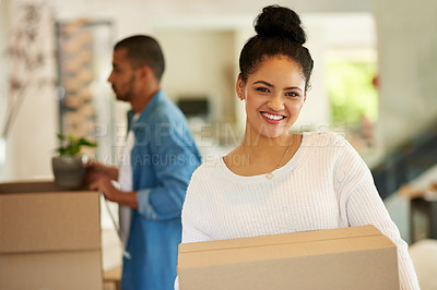 Buy stock photo Shot of a happy young woman carrying cardboard boxes into her new home with her boyfriend
