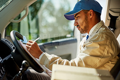 Buy stock photo Shot of a focused delivery man writing on a clipboard while sitting in his van