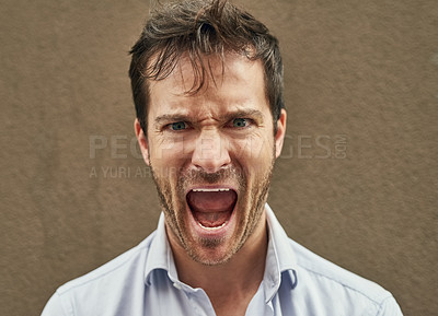 Buy stock photo Portrait of an angry young man standing against a dark background