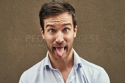 Buy stock photo Portrait of a young man pulling a funny face against a dark background
