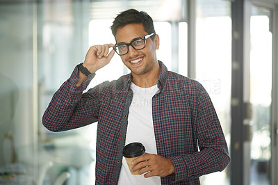 Buy stock photo Portrait of a handsome young designer holding a takeaway coffee while standing in his office