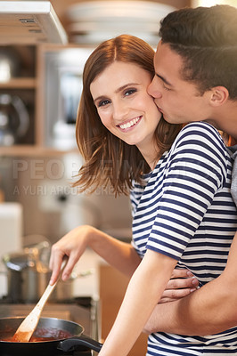 Buy stock photo Portrait of an affectionate young couple cooking a meal together in their kitchen