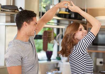 Buy stock photo Shot of a happy young couple dancing in their kitchen at home