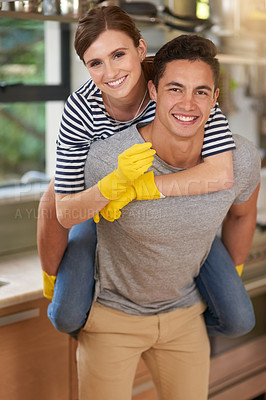 Buy stock photo Portrait of happy young man giving his wife a piggyback ride while they clean their kitchen