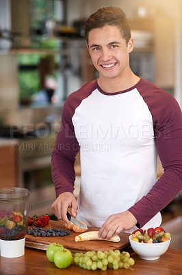 Buy stock photo Portrait of a happy young man preparing a healthy breakfast of fruit in his kitchen at home