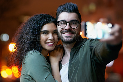Buy stock photo Shot of a happy young couple taking a selfie outdoors at night