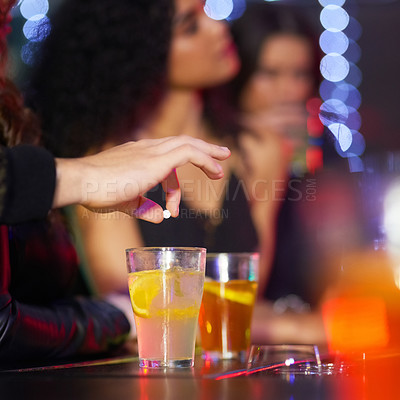 Buy stock photo Closeup shot of a man drugging a woman's drink in a nightclub