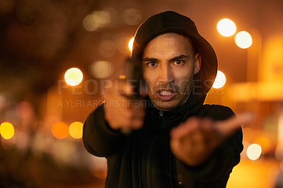 Buy stock photo Portrait of a gun-wielding thief aiming his weapon in the city