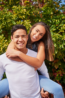 Buy stock photo Portrait of a smiling young man giving his girlfriend a piggyback outside